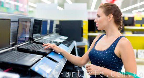 девушка выбирает ноутбук
